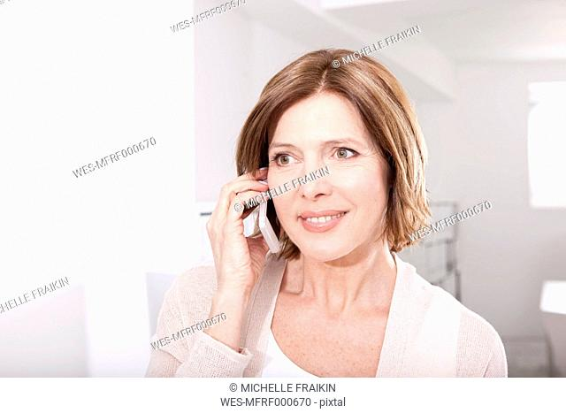 Portrait of smiling woman telephoning with smartphone in the office