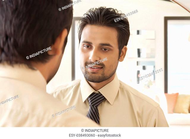 Businessman looking at self in mirror