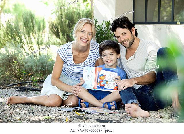 Parents together with child learning to read, portrait