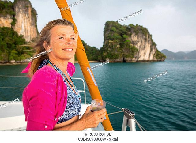 Woman sailing on yacht looking away smiling, Koh Hong, Thailand, Asia