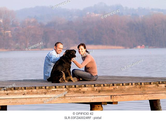 Couple petting dog on jetty over lake