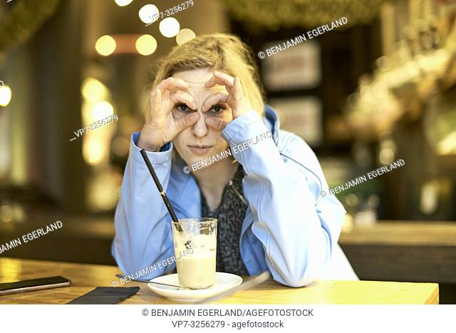 woman shaping rings around eyes, sitting in café, in Munich, Germany