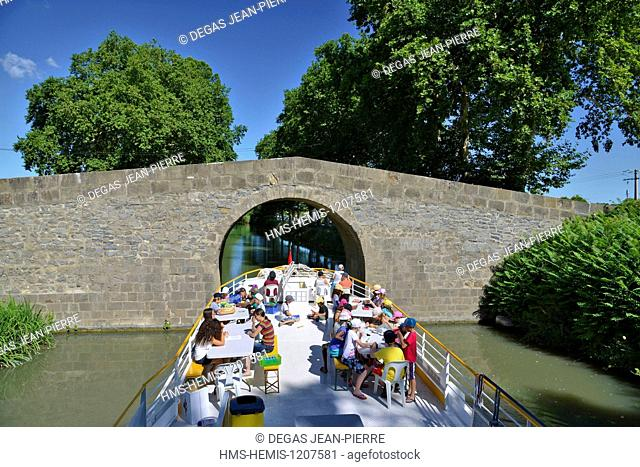 France, Herault, Cers, Canal du Midi listed as World Heritage by UNESCO, bridge of Caylus, children aboard a barge which gets ready to pass under a very narrow...