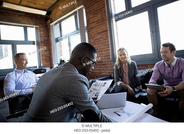 Business people reviewing proofs and blueprints in meeting