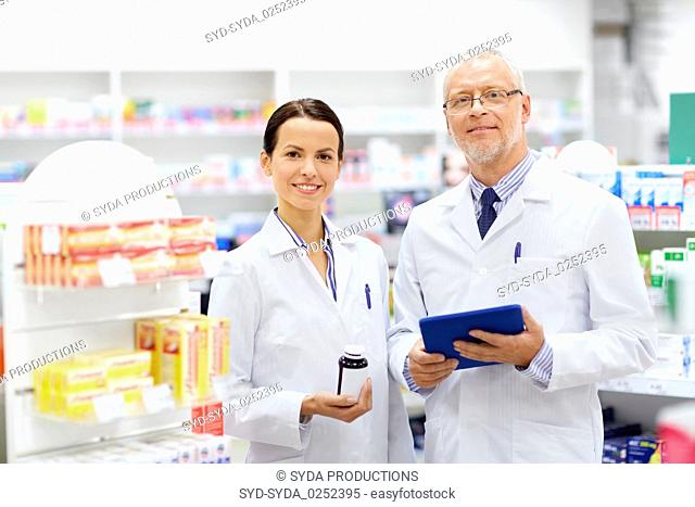 apothecaries with tablet pc and drug at pharmacy