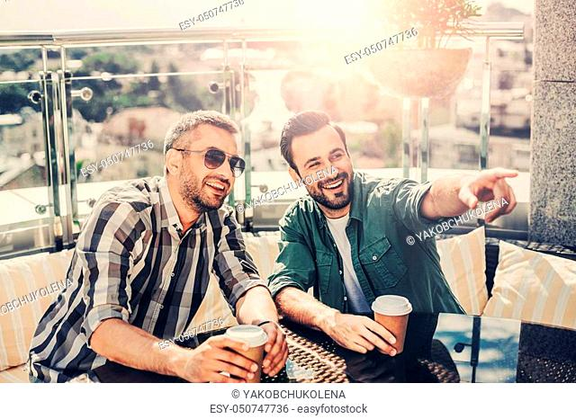Watch this. Cheerful fellows at outdoor cafe holding cups of coffee and laughing
