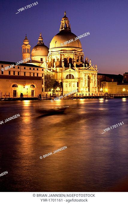 Grand Canal at dusk with Santa Maria della Salute and shadowy gondolas drifting by in Venice Veneto Italy