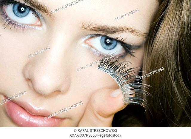 Young woman applying fake eyelashes