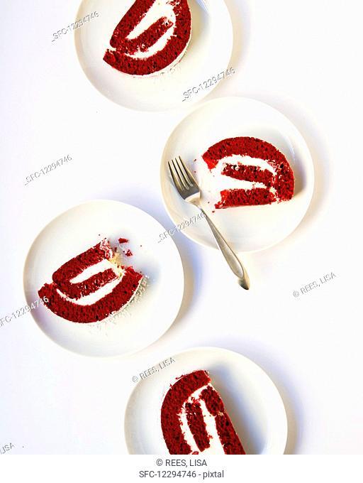 Slices of red velvet cake roll on dessert plates