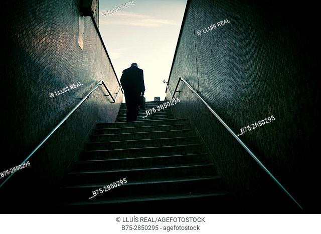 Ejecutivo de espaldas irreconocible con un portafolio en la mano subiendo unas escaleras. London Bridge, London, UK, Europa