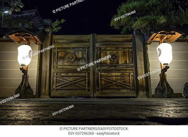 Illuminated lanterns in front of wooden doors to a temple gate on the road to Zenkoji in Nagano at night