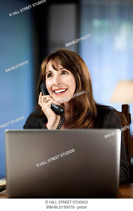 Caucasian woman using laptop and talking on telephone