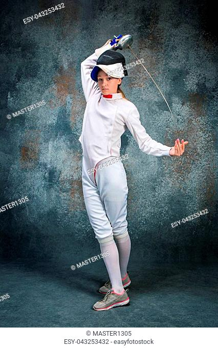 The woman wearing fencing suit posing with sword against gray studio background