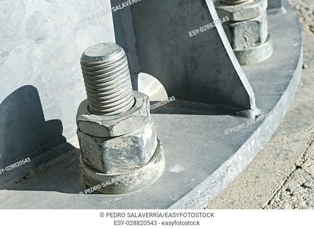 Close up of some larger screws into the base of a metal pillar