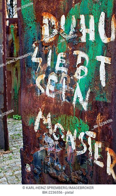 Graffiti on the rusty plate of a memorial outside Heilige Dreieinigkeitskirche, Holy Trinity Church, St. Georg quarter of Hamburg, Germany, Europe