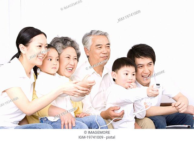 Grandchild playing video game, parents and grandparents looking smiling, portrait