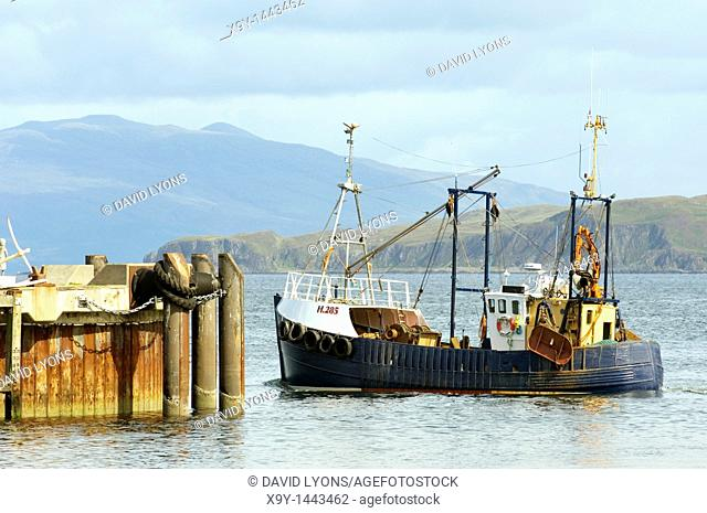 Fishing boat inshore trawler leaving Mallaig fishing port harbour on the Sound of Sleat in the western Highlands, Scotland, UK