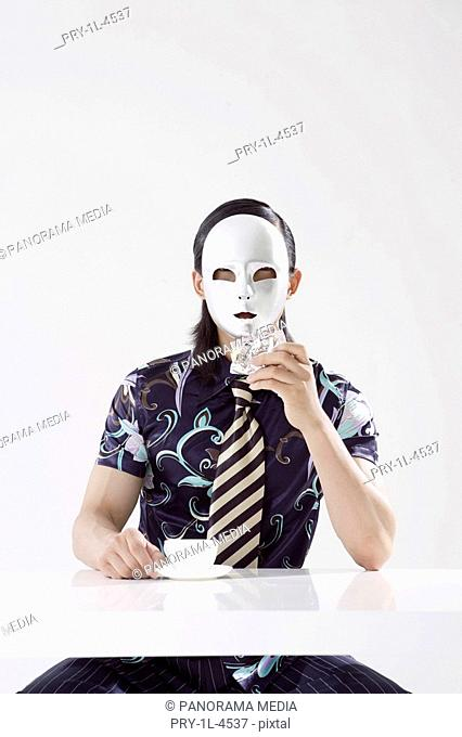 Young man wearing mask and holding cake