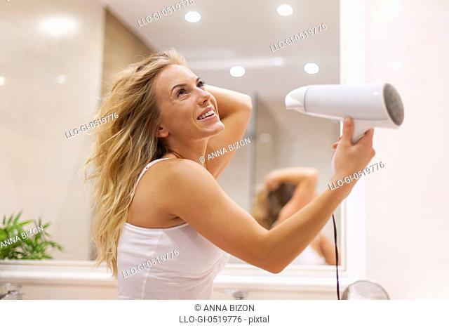 Blonde woman drying hair in bathroom. Debica, Poland