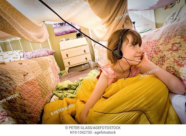 Preteen girl, with headphones, under a homemade bedroom tent