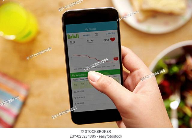 Person Eating Lunch Looking At Fitness App On Mobile Phone