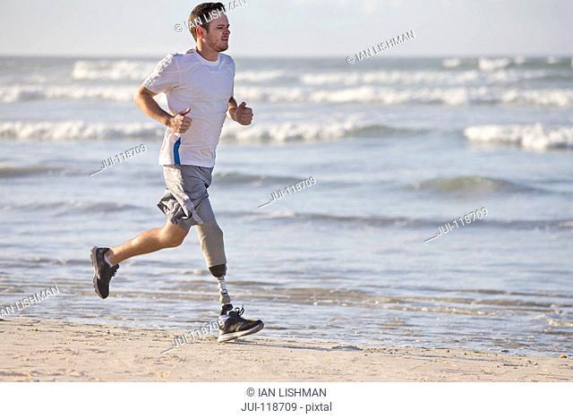 Man With Artificial Leg Running Along Beach