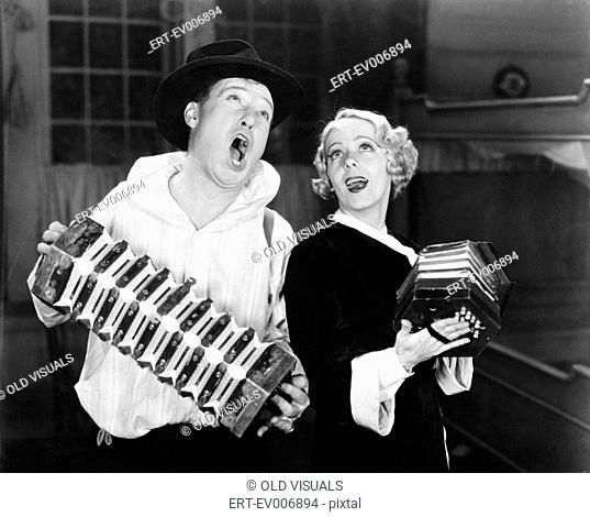 Couple singing while playing two accordions All persons depicted are not longer living and no estate exists Supplier warranties that there will be no model...