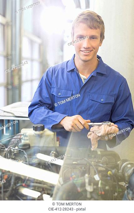 Portrait confident mechanic working on engine in auto repair shop