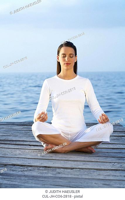 Young woman with eyes closed sitting cross legged on a dock