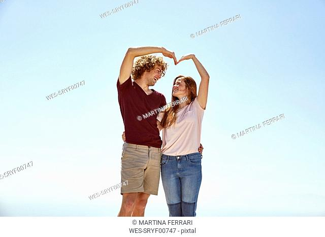 Happy young couple shaping a heart with their hands under blue sky