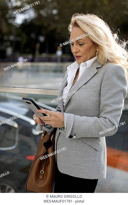 Senior businesswoman checking cell phone in the city