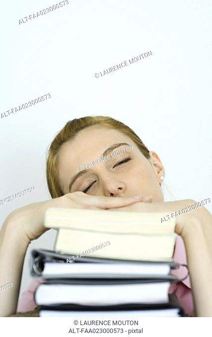 Young woman leaning on stack of books, eyes closed