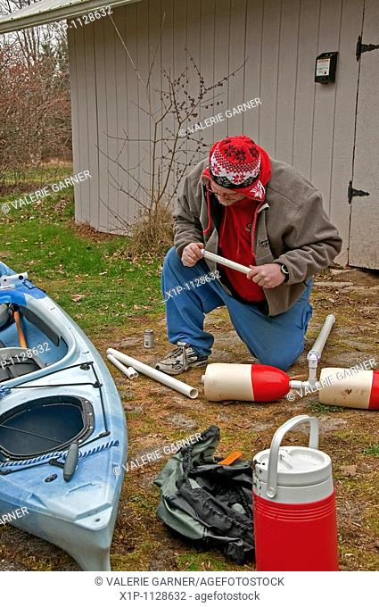 This middle aged man is preparing for kayak season in early spring by building an outrigger for his kayak out of PVC pipe