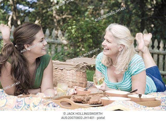 Mature woman with her daughter having picnic in a park