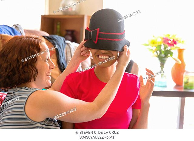 Young woman putting hat on smiling friends head, covering eyes