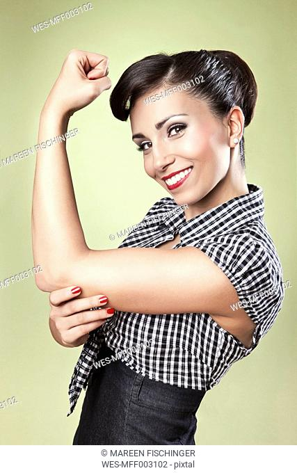 Positive woman in pin-up style lifting her arm