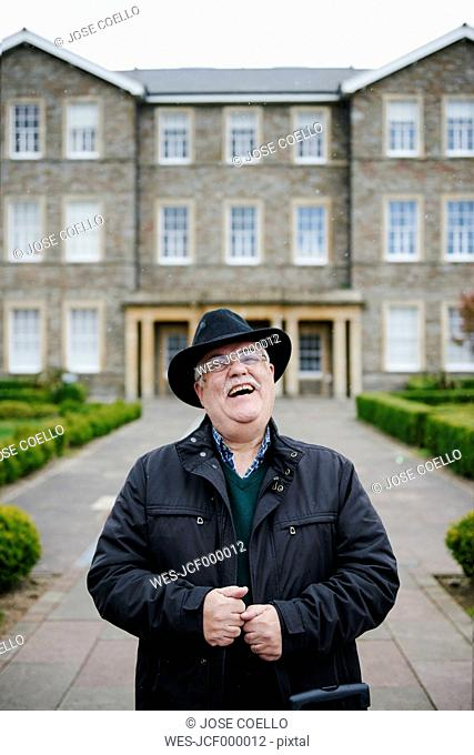 UK, Bristol, portrait of laughing senior man wearing black hat