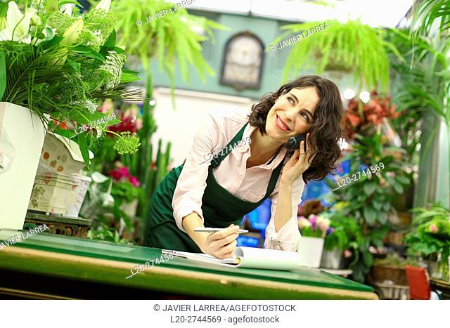 Florist in flower shop taking an order from a customer on the phone