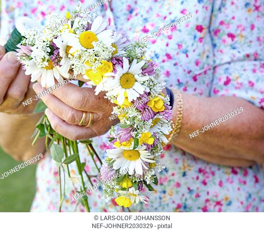 Senior woman making flower garland, close-up