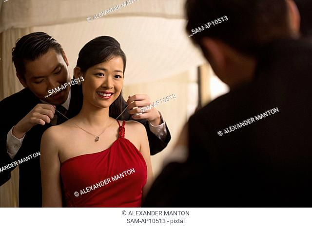 Singapore, Man putting necklace on woman in front of mirror