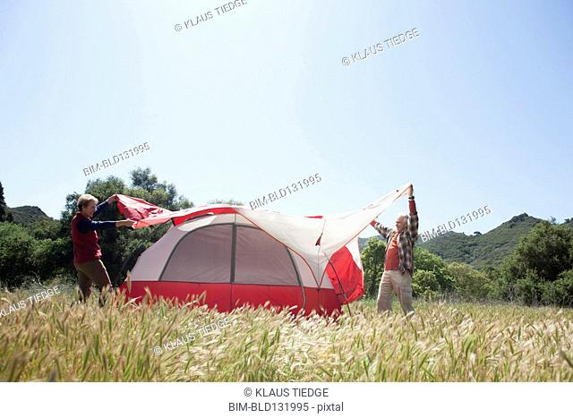 Senior Caucasian couple pitching tent in field