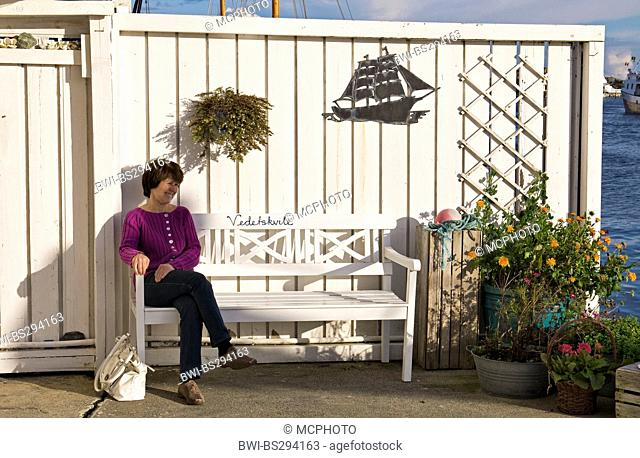woman sitting on a white bench in front of white wooden fence, Norway, Rogaland, Karmoy, Skudeneshavn