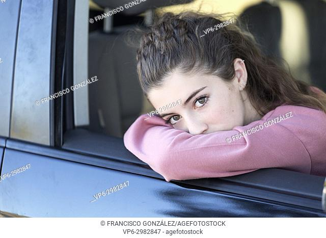 Teenage girl looking out the window of her car. Horizontal shot with natural light