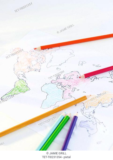 Colored pencils and map of world