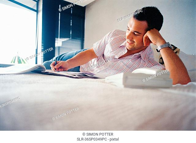 Smiling man writing on bed