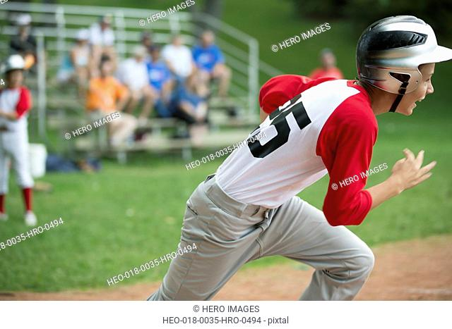 young male baseball player running to base