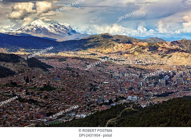 The city of La Paz with Illimani rising in the distance, the highest peak in Bolivia; La Paz, Bolivia