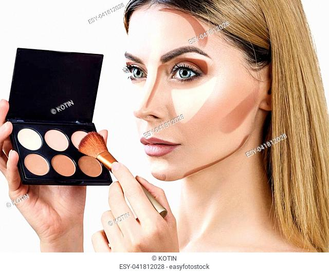 Portrait of adult woman holding palette for contouring face. Isolated on white background