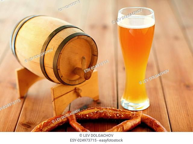 brewery, drinks and alcohol concept - close up of draft lager beer in glass, pretzel and wooden barrel on table