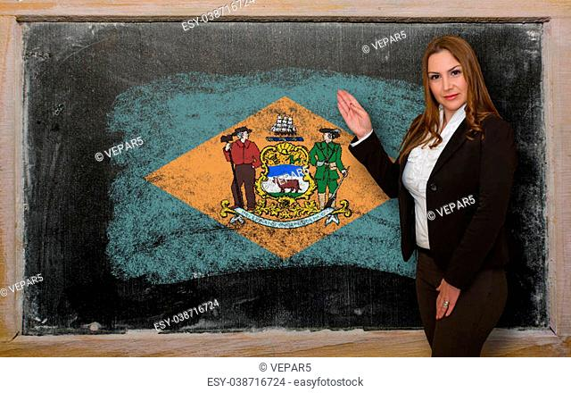 Successful, beautiful and confident woman showing flag of delaware on blackboard for marketing research, presentation and tourist advertising